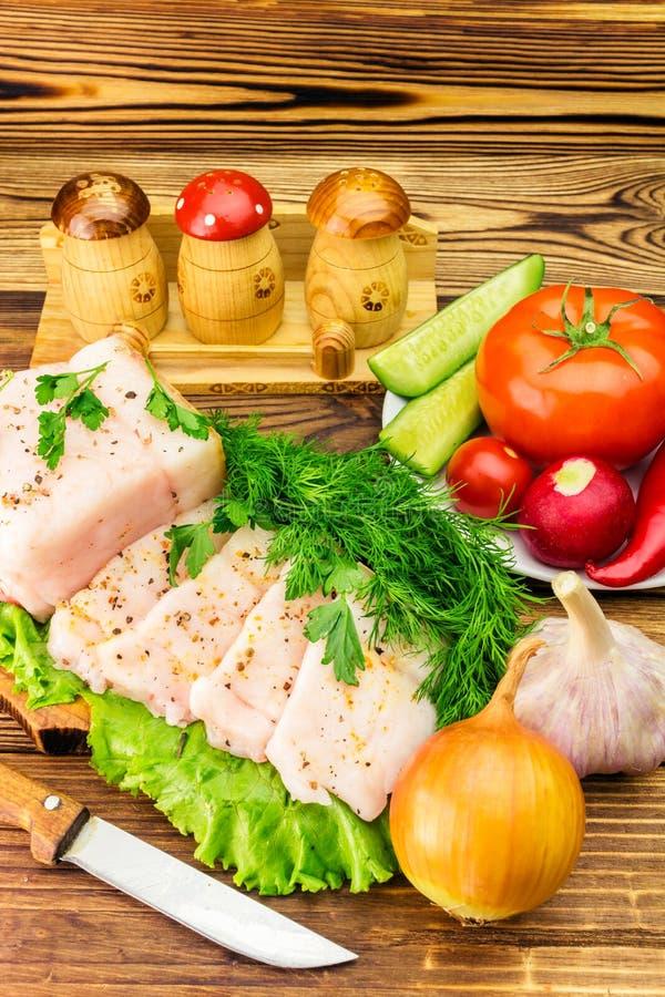 Stuk en gesneden verse varkensvleesreuzel, vers product, greens, groenten op de houten raad en mes op lijst stock afbeelding