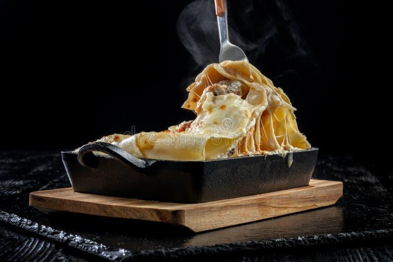 Stuk smakelijke hete lasagna's Traditionele Italiaanse lasagna's op een gietijzerpan royalty-vrije stock fotografie