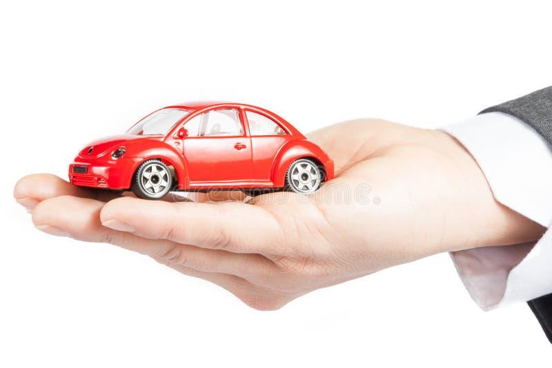 Stuk speelgoed auto in de hand van bedrijfsmensenconcept voor verzekering, het kopen, het huren, brandstof of de dienst en reparat royalty-vrije stock afbeelding
