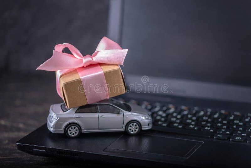 Stuk speelgoed auto en giftdoos op laptop toetsenbord op donkere achtergrond Online het winkelen voertuigen op Internet royalty-vrije stock afbeelding