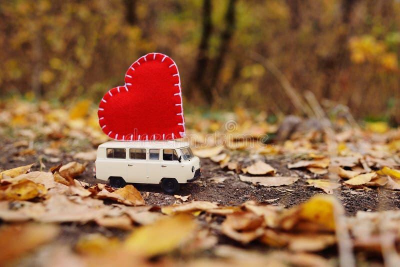 Stuk speelgoed auto minivan gelukkig op het dak van een groot rood hart op de bedelaars royalty-vrije stock foto