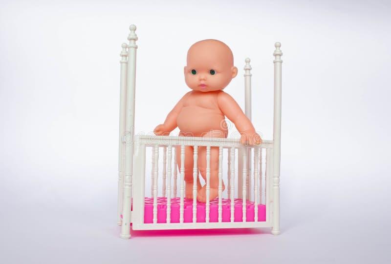 Stuk speelgoed baby in de voederbak Wit kinderdagverblijf voor jonge kinderen Weinig jongen die zich in zijn voederbak leren te b stock foto