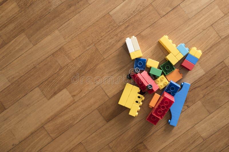 Stuk speelgoed bakstenen op houten vloer Kleurrijke plastic blokken stock afbeelding
