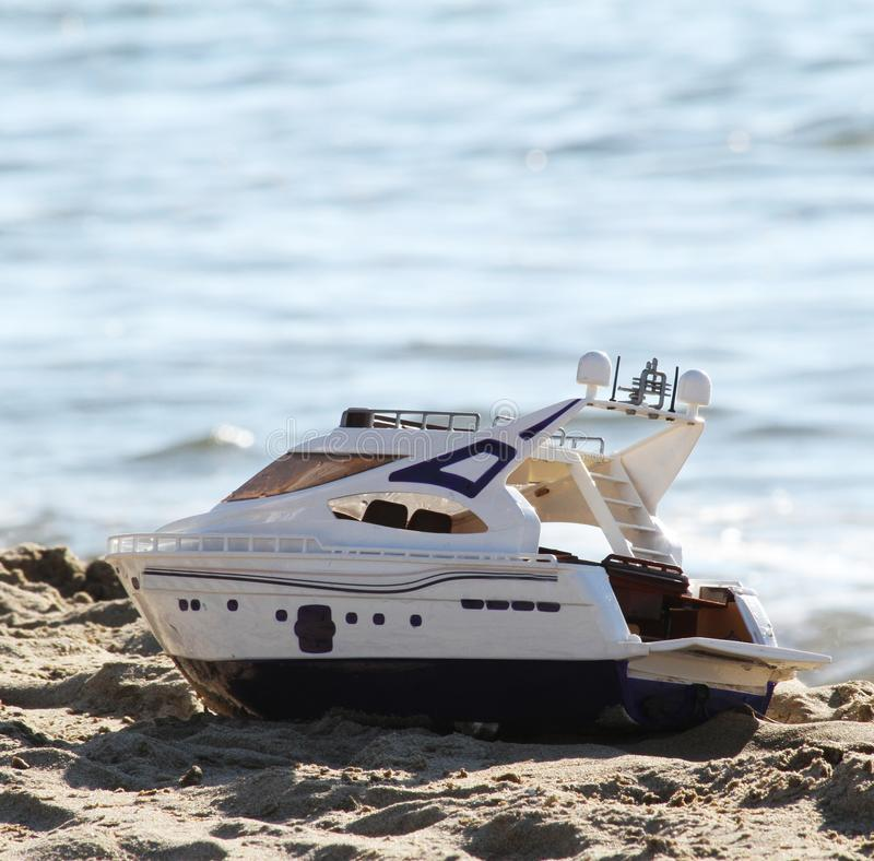 Stuk speelgoed boot op het strand stock afbeelding