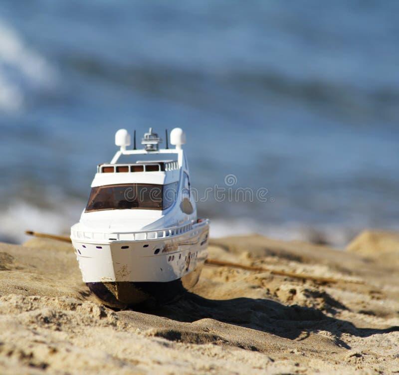 Stuk speelgoed boot op het strand royalty-vrije stock foto's