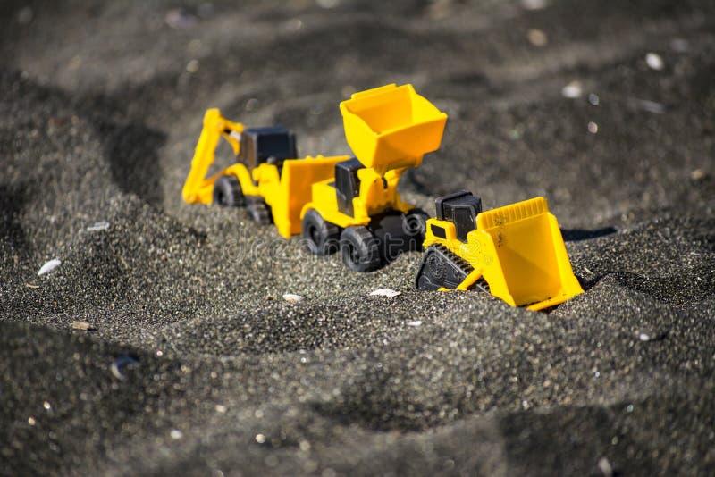 Stuk speelgoed bouwmachines in zwart zand stock foto