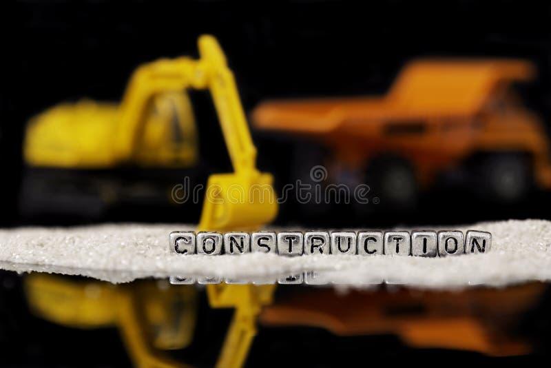 Stuk speelgoed bouwvoertuigen en zand met de woordbouw op parels stock foto's