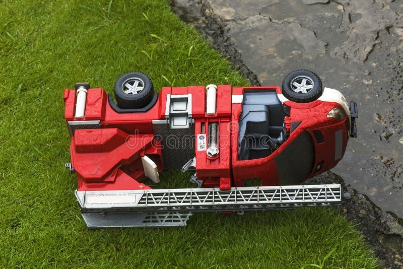 Stuk speelgoed brandmotor die op het gras eenzaam in de regen wordt verlaten stock foto's