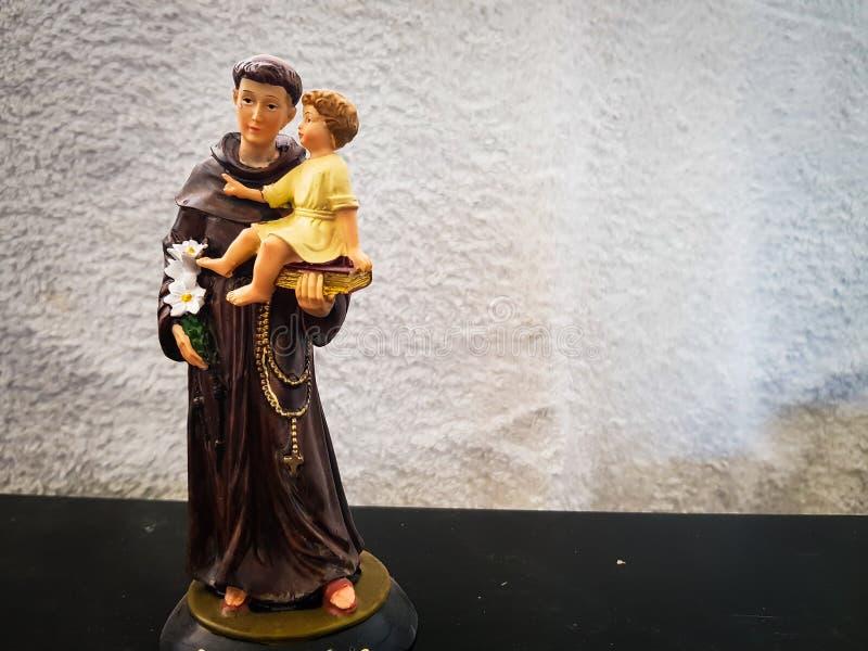 Stuk speelgoed cijfer die van heilige Anthony een jongenskind houden stock foto