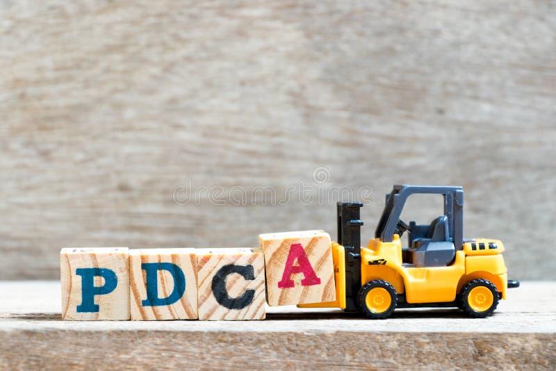 Stuk speelgoed de brief van de vorkheftruckgreep blokkeert A aan volledig woordpdca Plan, controleert, handelen stock afbeelding
