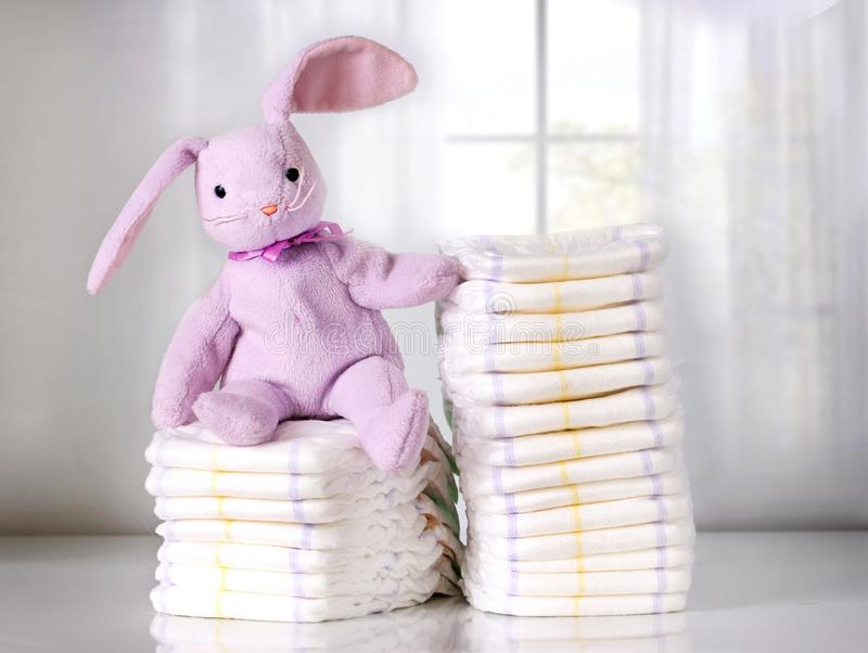 Stuk speelgoed de konijntjeszitting op Stapel beschikbare luiers of nappies, Stapel luiers, vertroetelt royalty-vrije stock foto's