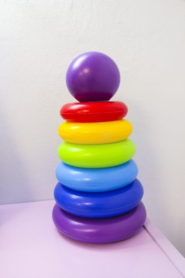 Stuk speelgoed de piramide van kinderen voor ontwikkeling van intelligentie en motiliteit op lichte weefselachtergrond royalty-vrije stock foto