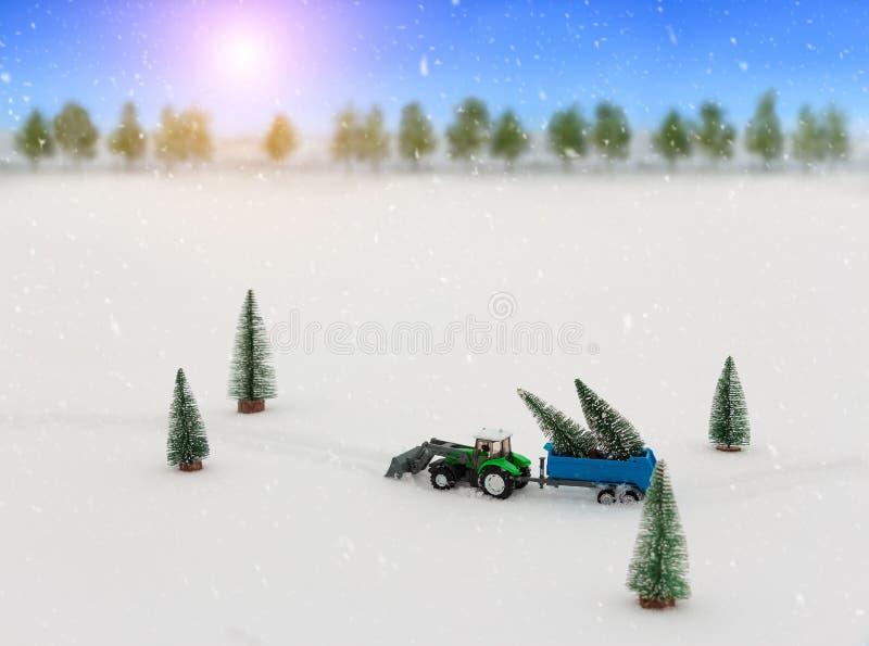 Stuk speelgoed de tractor met een aanhangwagen draagt Kerstbomen tijdens sneeuwval, berijdt door de sneeuw in het midden van het  royalty-vrije stock fotografie