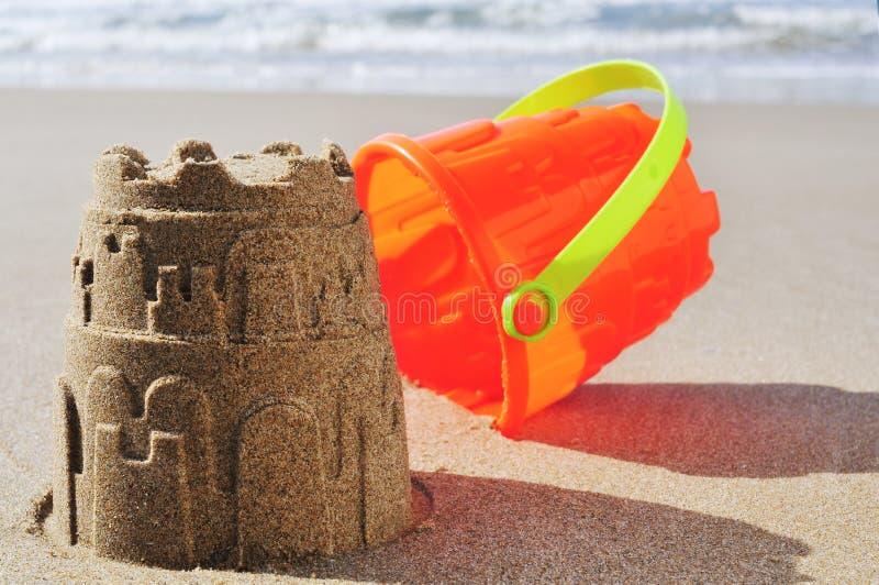 Stuk speelgoed emmerzandkasteel op het zand van een strand stock afbeelding