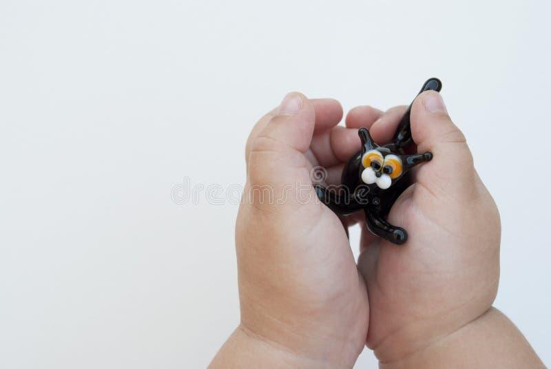 Stuk speelgoed glas zwarte kat in de handen van een jong kind op een witte achtergrond Gele ogen stock afbeelding
