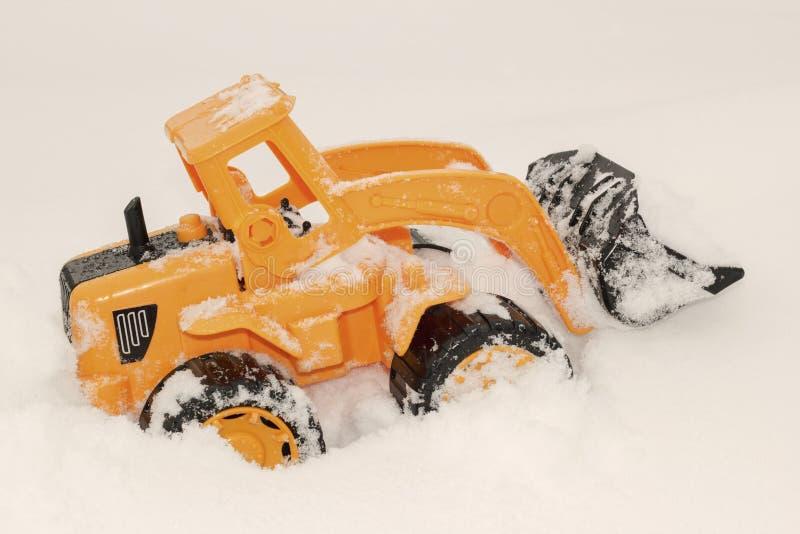 Stuk speelgoed graafwerktuig in de sneeuw stock foto's