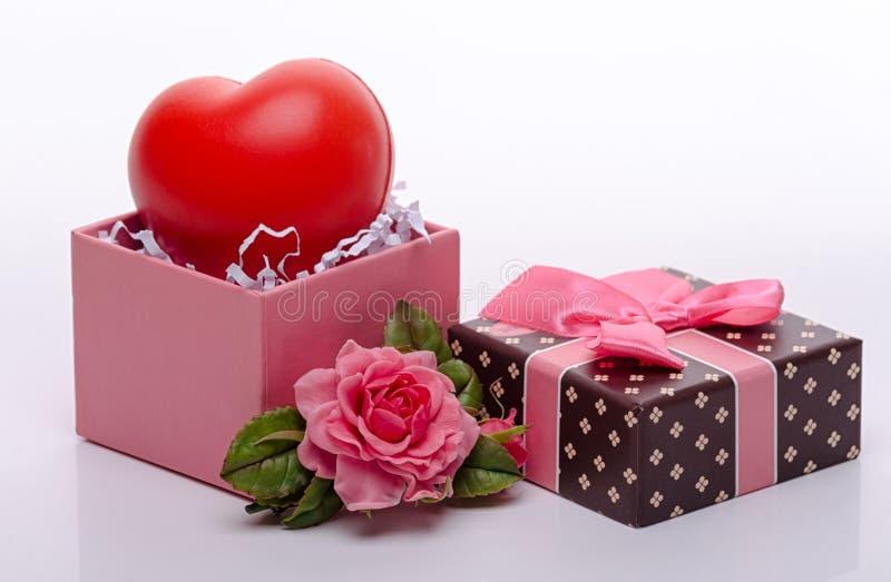 Stuk speelgoed hart in een open roze kartondoos met een boog van roze lint en juwelen in de vorm van een roos, een gift aan het m royalty-vrije stock foto