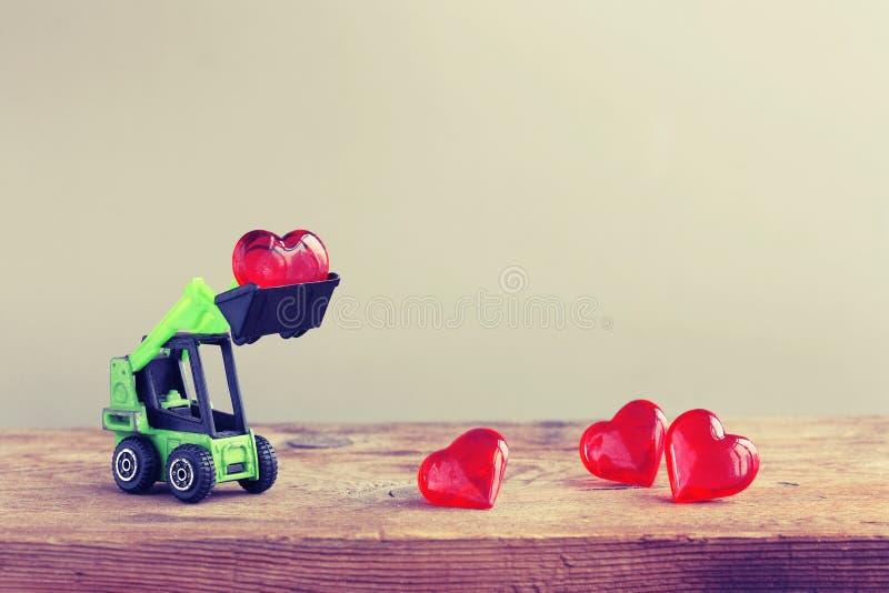 Stuk speelgoed het graafwerktuig laadt hart op houten lijst stock foto's