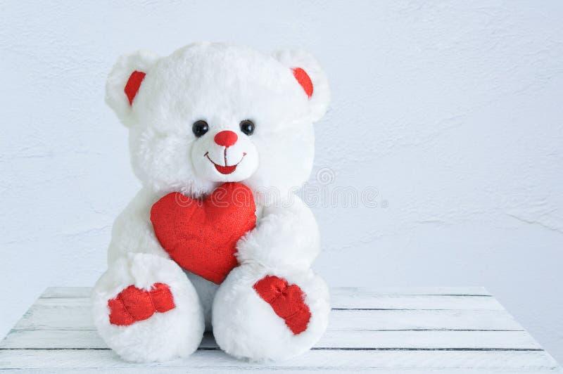 Stuk speelgoed het wit draagt met een hart in zijn handen stock foto's