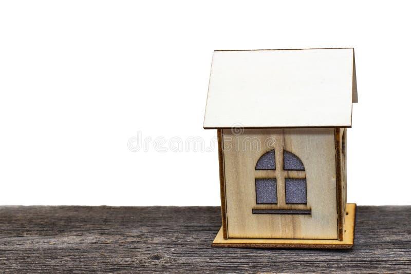 Stuk speelgoed huis met sleutels en contant geld op oude houten Raad, op wit geïsoleerde achtergrond royalty-vrije stock foto's