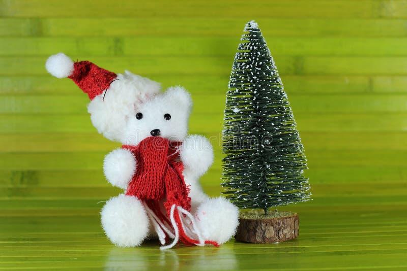 Stuk speelgoed ijsbeerwelp met een hoed en een rode sjaalzitting naast een decoratieve chrismasboom op groene houten achtergrond royalty-vrije stock foto