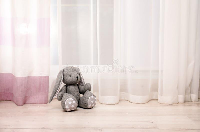 Stuk speelgoed konijn op vloer dichtbij venster in kindruimte stock foto