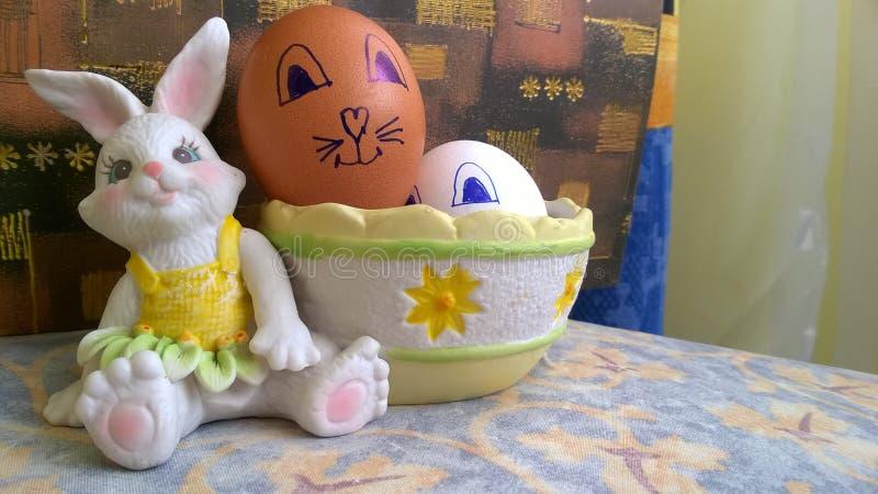 Stuk speelgoed konijntje met mand en paaseieren stock foto's