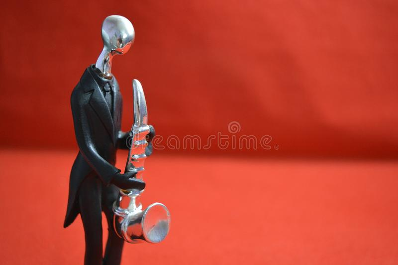 Stuk speelgoed mens met saxaphone op rode achtergrond royalty-vrije stock foto's