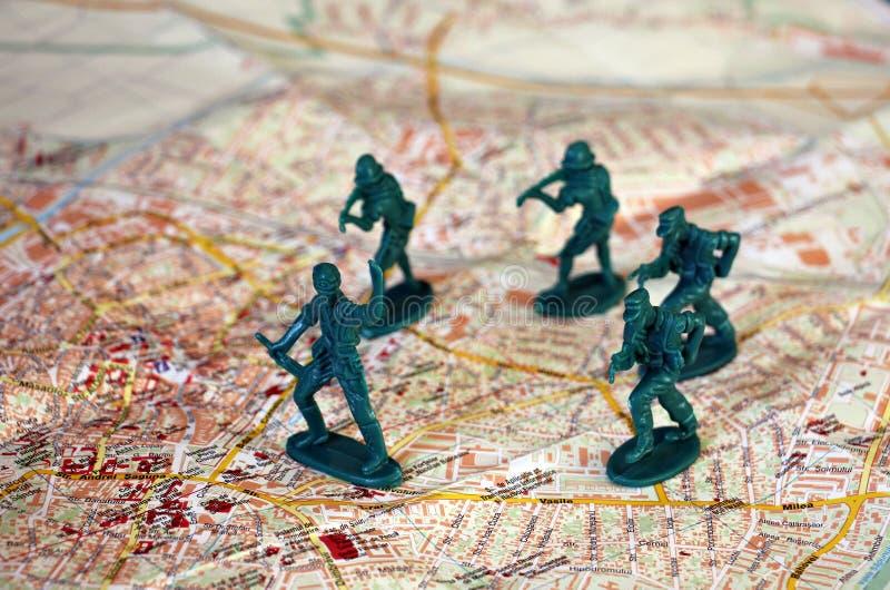 Stuk speelgoed militairen die op een kaart vechten royalty-vrije stock afbeeldingen