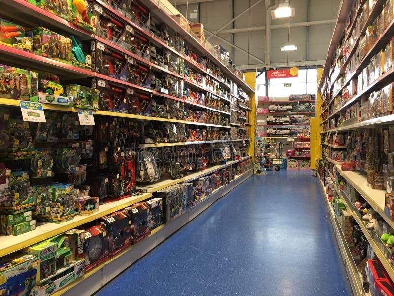 Stuk speelgoed planken bij het Smyths-Speelgoed Superstore stock afbeelding
