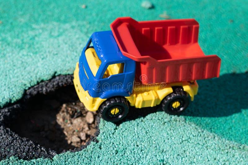 Stuk speelgoed plastic vrachtwagen met een rood die lichaam voor de kuil wordt tegengehouden De auto kan niet gaan Gat op asfalt  royalty-vrije stock foto's