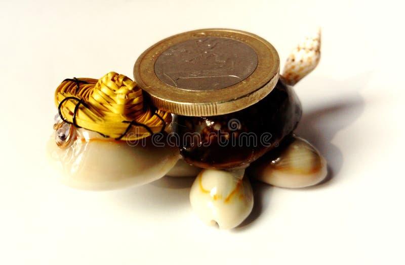 Stuk speelgoed schildpad met euro muntstuk royalty-vrije stock foto