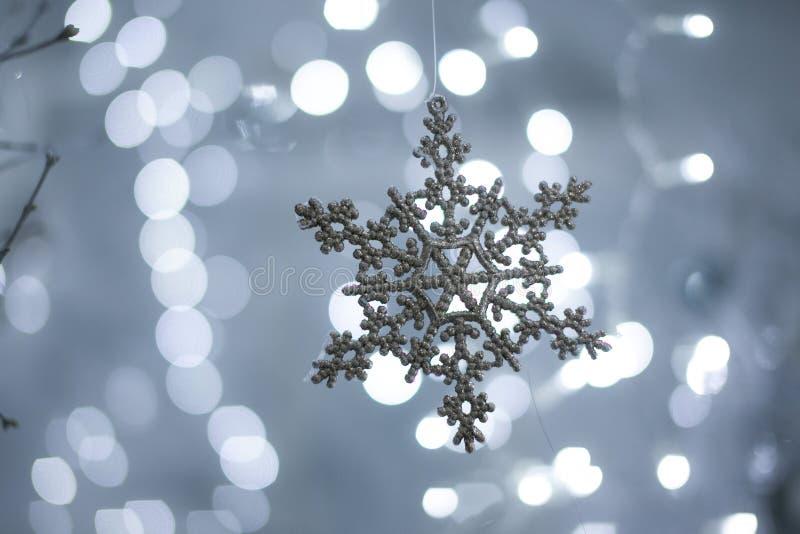 Stuk speelgoed sneeuwvlok op bokehachtergrond stock foto