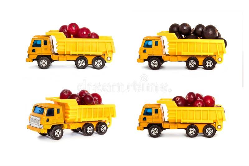 Stuk speelgoed stortplaatsvrachtwagens met bessen worden geladen die stock afbeelding
