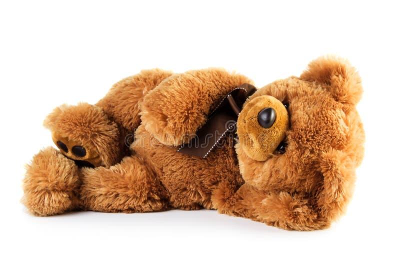 Stuk speelgoed teddybeer het liggen royalty-vrije stock fotografie
