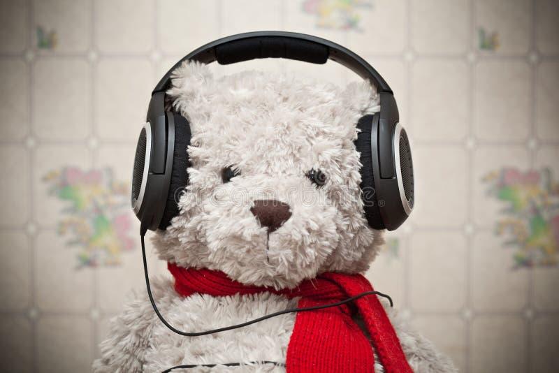 Stuk speelgoed teddybeer met een rode sjaal die aan muziek op hoofdtelefoons luisteren stock afbeelding