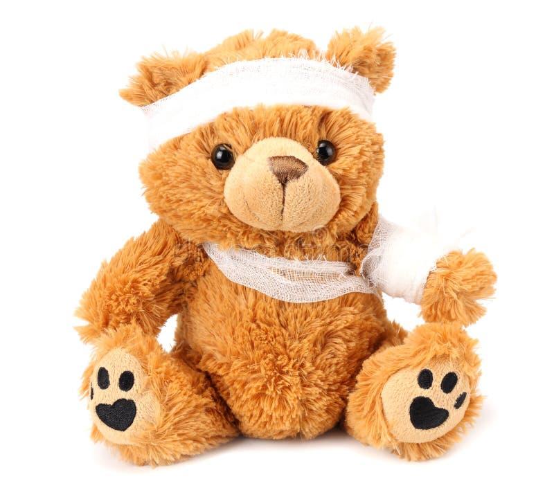 stuk speelgoed teddybeer met verband die op witte achtergrond wordt geïsoleerd royalty-vrije stock afbeelding