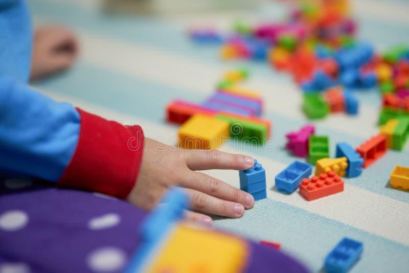 Stuk speelgoed van de aanrakings het kleurrijke bakstenen van de jong geitjehand op matvloer voor het spelen royalty-vrije stock fotografie
