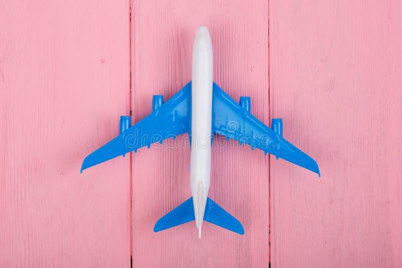 Stuk speelgoed vliegtuig op roze houten achtergrond