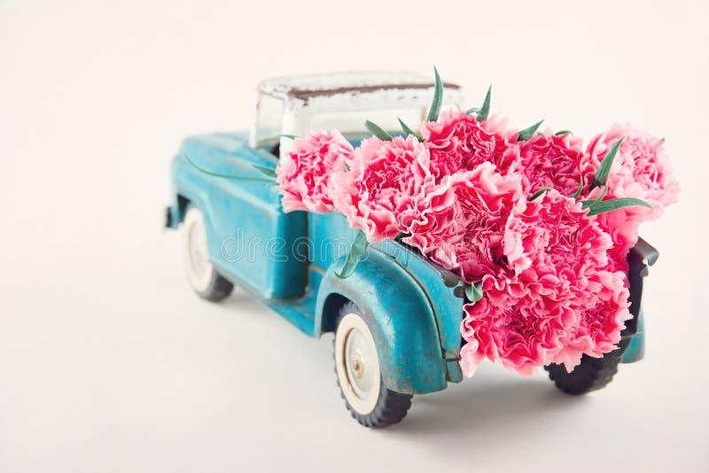 Stuk speelgoed vrachtwagen die roze anjers dragen royalty-vrije stock foto