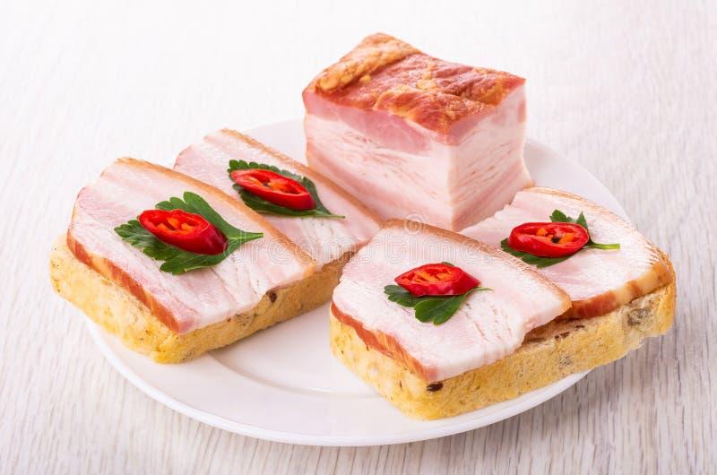 Stuk van borststuk, sandwiches met borststuk, Spaanse peperpeper, peterselie in plaat op lijst stock afbeelding
