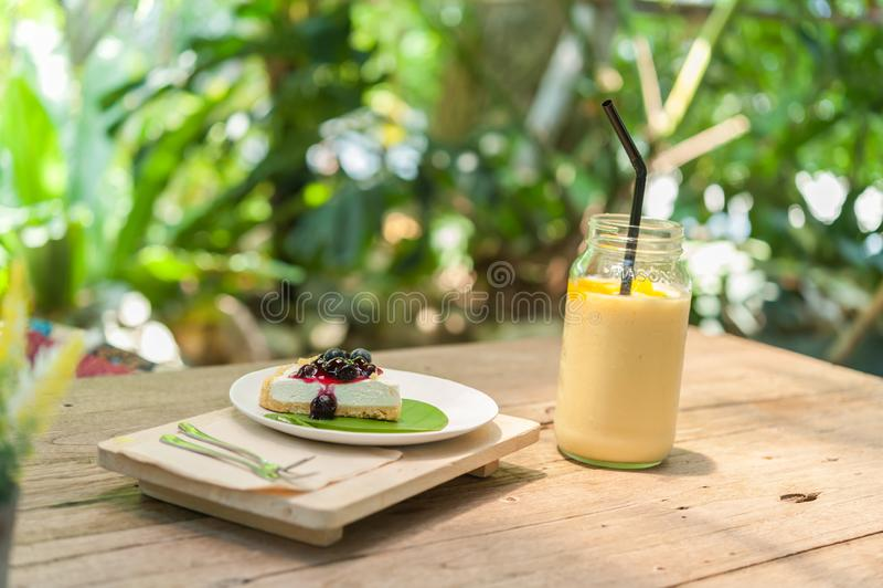 Stuk van bosbessenkaastaart met mangoyoghurt smoothie stock foto