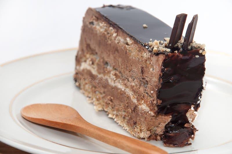 Stuk van chocoladecake met houten lepel op de plaat royalty-vrije stock foto's
