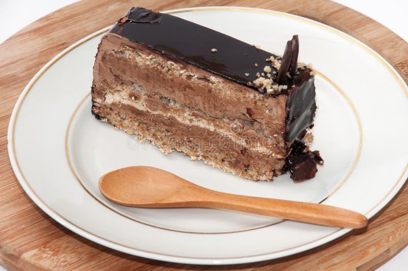 Stuk van chocoladecake met houten lepel op de plaat stock foto's