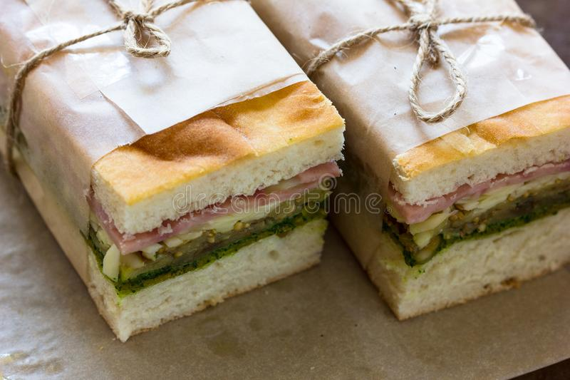 Stuk van de kaas van de sandwichham met sla en tomaat op houten plaat Eigengemaakte die sandwich met jus d'orange voor ontbijt wo stock foto