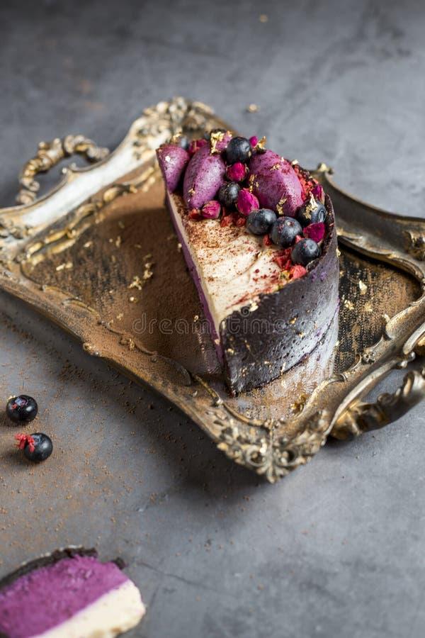 Stuk van de smakelijke cake die met fruit op een gouden dienbladkosten wordt verfraaid op een grijze achtergrond stock afbeelding