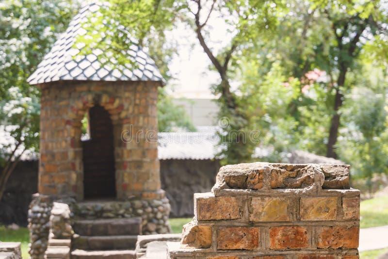 Stuk van een geruïneerde bakstenen muur op de achtergrond van watchtower op een speelplaats in de stijl van een middeleeuws kaste stock foto's