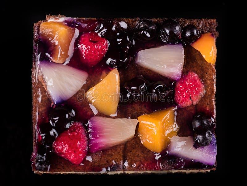 Stuk van fruitcake met gelei en room Zwarte achtergrond Hoogste mening stock foto