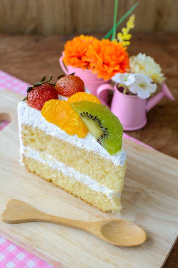 Stuk van fruitcake met kiwi, aardbei en sinaasappel royalty-vrije stock foto's