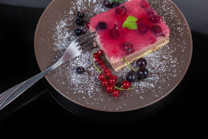 Stuk van gelaagde cake met verse bessen op schotel, vork royalty-vrije stock afbeeldingen